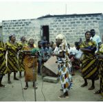 An Apatampa group of Anomabu perform outside a small grey brick building