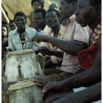 A crowd of Akom drummers playing outside