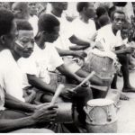 Two players of the Adawur Bells flank drummers at an outdoor akom event