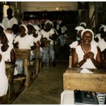 Women sit in rows of desks at an Awerekyekyer meeting in Anomabu