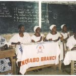 Four Officers of Anomabu's Awerekyekyer Branch sit at a table in front of a chalkboard, all on one side behind a banner
