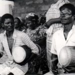 Two Dondo Players of the Anomabu Adenkum Group perform while seated with drums