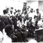 The Kolomashie gather sitting and standing in a small room